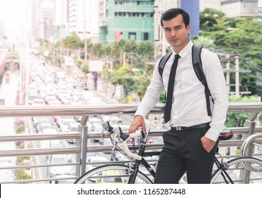 Modern Business man is cycling bicycle to work to avoid traffic jam in busy city