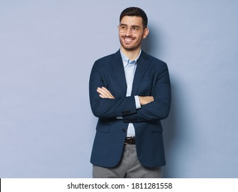 Modern business man standing in smart casual suit, holding crossed arms, smiling and looking aside, isolated on blue background, copy space on left