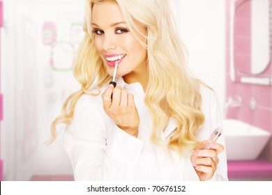 modern business woman applying makeup in pink bathroom