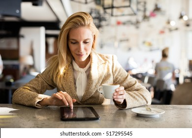 Modern business woman in city cafe. Drinking coffee and surfing the web. Coffee break.