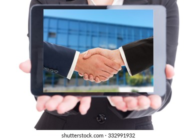 Modern business woman holding wireless tablet with businesspeople handshake on screen  or display