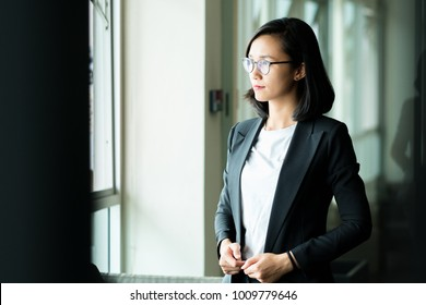 Modern business woman in the office  looking out the window with copy space
