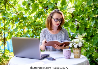 Modern business woman reading and makes notes, sits at a work desk in nature. The concept of freelancing, remote work and digital nomad.
