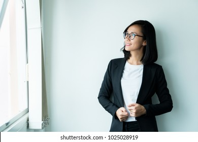 Modern business woman standing looking out window in the office with copy space