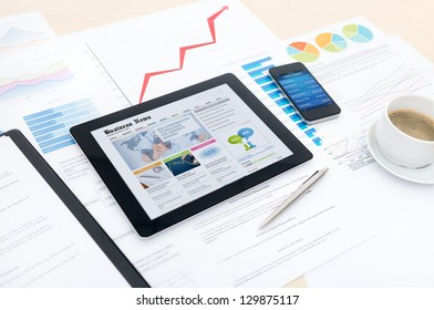 Modern business workplace with business news website on digital tablet, mobile banking on a smartphone and some charts and graphs on a desktop.