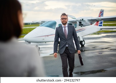 Modern businessman with briefcase hurrying to meet his partner