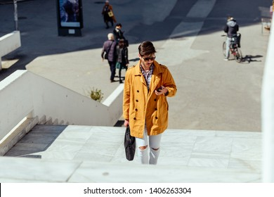 Modern businessman with briefcase texting on his cellphone at urban place, calling for a taxi ride, e-hailing