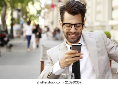 Modern businessman and business woman sitting at coffee shop and using mobile. Business people.
