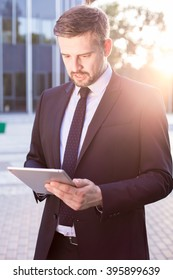 Modern businessman checking the market on his tablet
