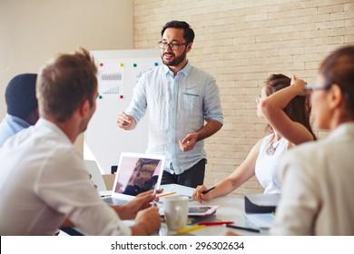 Modern businessman explaining his ideas to colleagues at seminar
