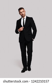 Modern businessman. Full length of handsome young man in full suit keeping hands in pockets and looking away while standing against grey background