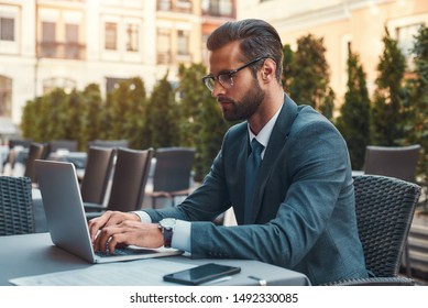 Modern businessman. Portrait of handsome bearded businessman in eyeglasses working with laptop while sitting in restaurant outdoors