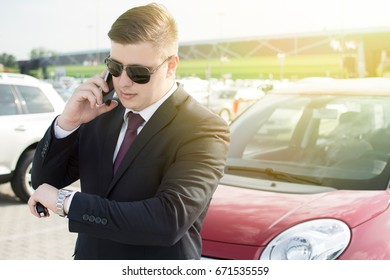 Modern businessman standing in a parking lot. Making a phone call while looking at his watch. Lens Flare in the background.