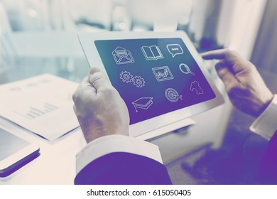 Modern businessman taking online course of business and economics via mobile table in office