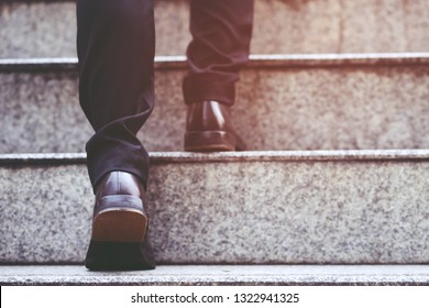 modern businessman working  close-up legs walking up the stairs in modern city. in rush hour to work in office a hurry. During the first morning of work. stairway. soft focus.