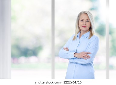 Modern businesswoman. Beautiful middle aged woman looking at camera with a smile, standing in the office near the window.Female face close-up
