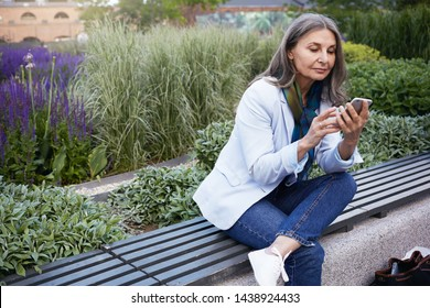 Modern busy middle aged female in fashionable clothes spending summer evening outdoors, sitting comfortably on wooden bench with electronic gadget. Stylish mature lady using mobile phone in park
