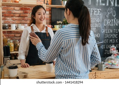 In modern cafe friendly woman worker make takeaway coffee for office lady customer who pay by contactless mobile phone to credit card system. client showing online payment on smartphone to waitress