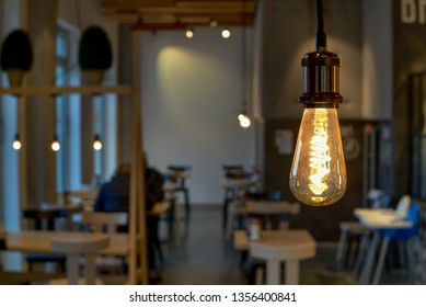 Modern Cafe interior with focus on classic light bulb and strong bokeh background