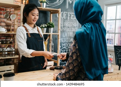 Modern cafe start up small business micropayment concept. Female waitress interacting with islam customer using bank terminal to process and acquire credit card payments in coffee shop on sunny day.