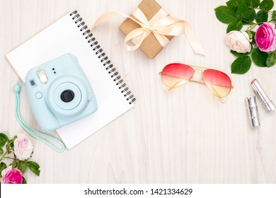 Modern camera, gift box, sunglasses, feminine accessories, roses on wooden background. Top view, tender minimal flat lay style composition. Women desk, fashion blogger, beauty technology