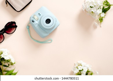 Modern camera, sunglasses, white flowers on pastel pink color background. Top view, tender minimal flat lay style composition. Women desk, fashion blogger, beauty technology