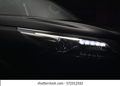 A Modern car Close up of Headlight on Black Tone