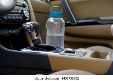 modern car in cup holder for water bottle.  drinking water bottle in a car.