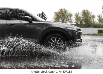 Modern car driving outdoors on rainy day