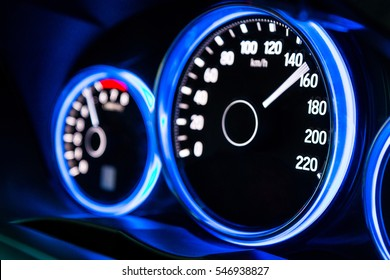 Modern car instrument panel dashboard with blue illuminated display, rev up. (Selective focus and shallow depth of field)