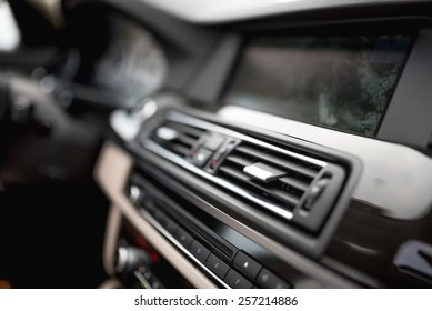 modern car interior with close-up of ventilation system holes and air conditioning. Concept wallpaper for auto air conditioning and dashboard