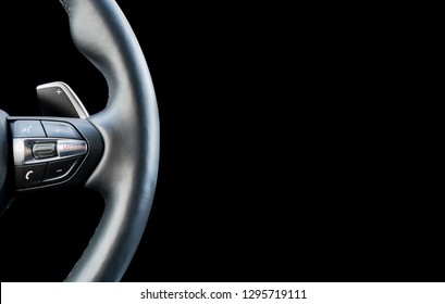 Modern car interior. Steering wheel with media phone control buttons isolated on black background. Car interior details. Car detailing