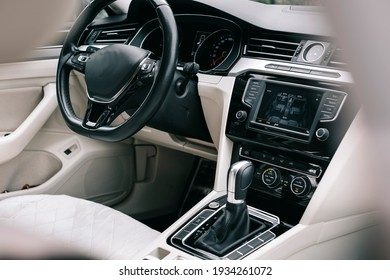 Modern car interior, white perforated leather, aluminum, black lacquer, leather steering wheel.