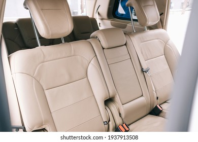 Modern car interior, white perforated leather, aluminum, controls.