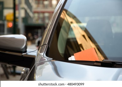 Modern car with a parking ticket on its window in New York City.