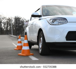 Modern car and safety cones in driving school outdoors