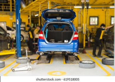 modern car service. back view of blue car in yellow room service. Wheel replacement. Body shop. industrial background