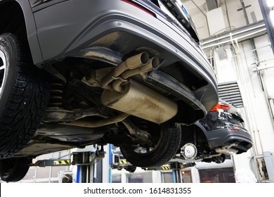 A modern car SUV in a service center is lifted on a lift for diagnosis, maintenance or repair. Close-up back of a car, muffler, bumper trim, exhaust pipe. Service station in the background is blurred.
