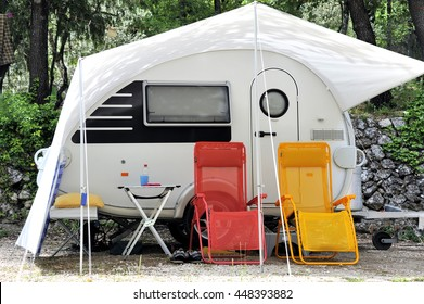 Modern caravan with in front two colored camping chairs