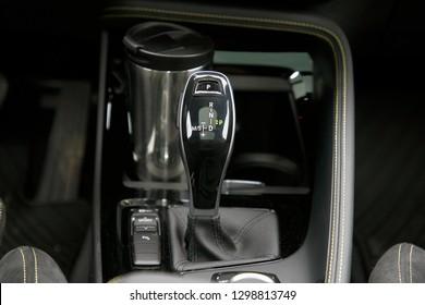 modern car's gearshift lever and coffee mug behind