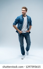 Modern and casual. Full length of handsome young man looking at camera with smile whilestanding against grey background