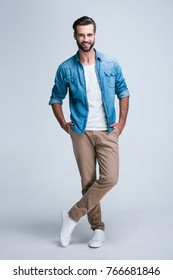 Modern and casual. Full length of handsome young man looking at camera with smile while standing against white background