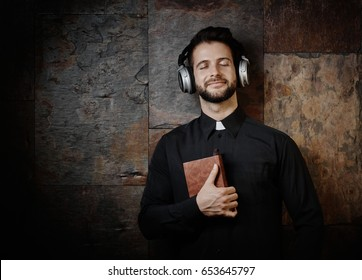 Modern catholic priest listening music on headphones with closed eyes.