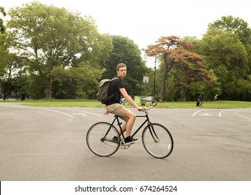 Modern Caucasian college student riding bike in the park, photographed in Brooklyn, NY in July 2017