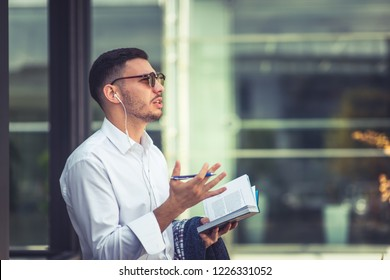 Modern Caucasian man holding notebook and pen while listening music. Urban businessman on the move