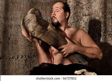 Modern caveman staring at mammoth femur bone