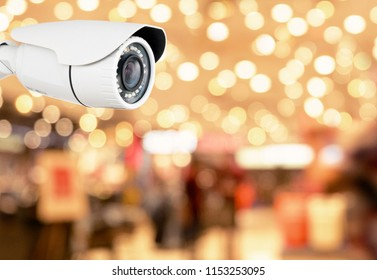 Modern CCTV camera on a wall. A blurred with shop store background.