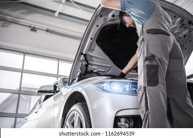 Modern Certified Car Service. Caucasian Mechanic in His 30s Checking Crucial Elements of the Engine During Scheduled Warranty Maintenance.