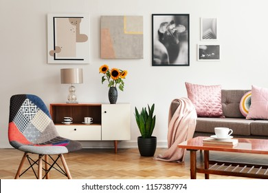 Modern chair and sunflowers on cabinet in flat interior with posters and pink pillows on sofa. Real photo