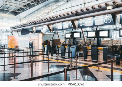 Modern check-in zone of airport: luggage accept terminals with baggage handling belt conveyor systems, numerous empty information LCD screen mockups, indexed check-in desks with digits above